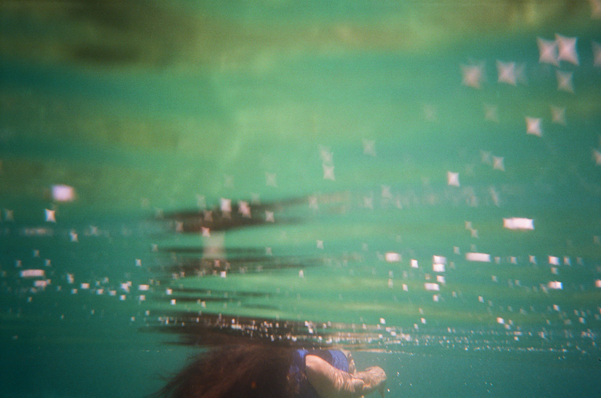 A color photograph taken underwater of a person floating on their back up at the surface. Their reflection repeats in the gentle undulations of the clear turquoise water, and the sunlight shimmers in many little four-pointed stars.