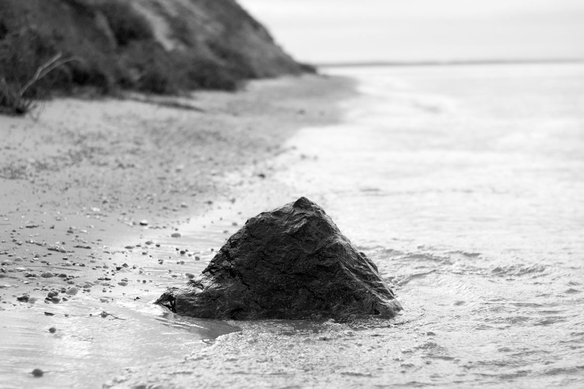 A black and white photograph of a pyramid-shaped basalt stone, the size of a small stool, embedded in the sand at the waterline on a sandy beach. The water is calm and bright, with a low swell washing gently around the stone, and to the left in the background a steep, dark bluff rises from the sand out of frame.