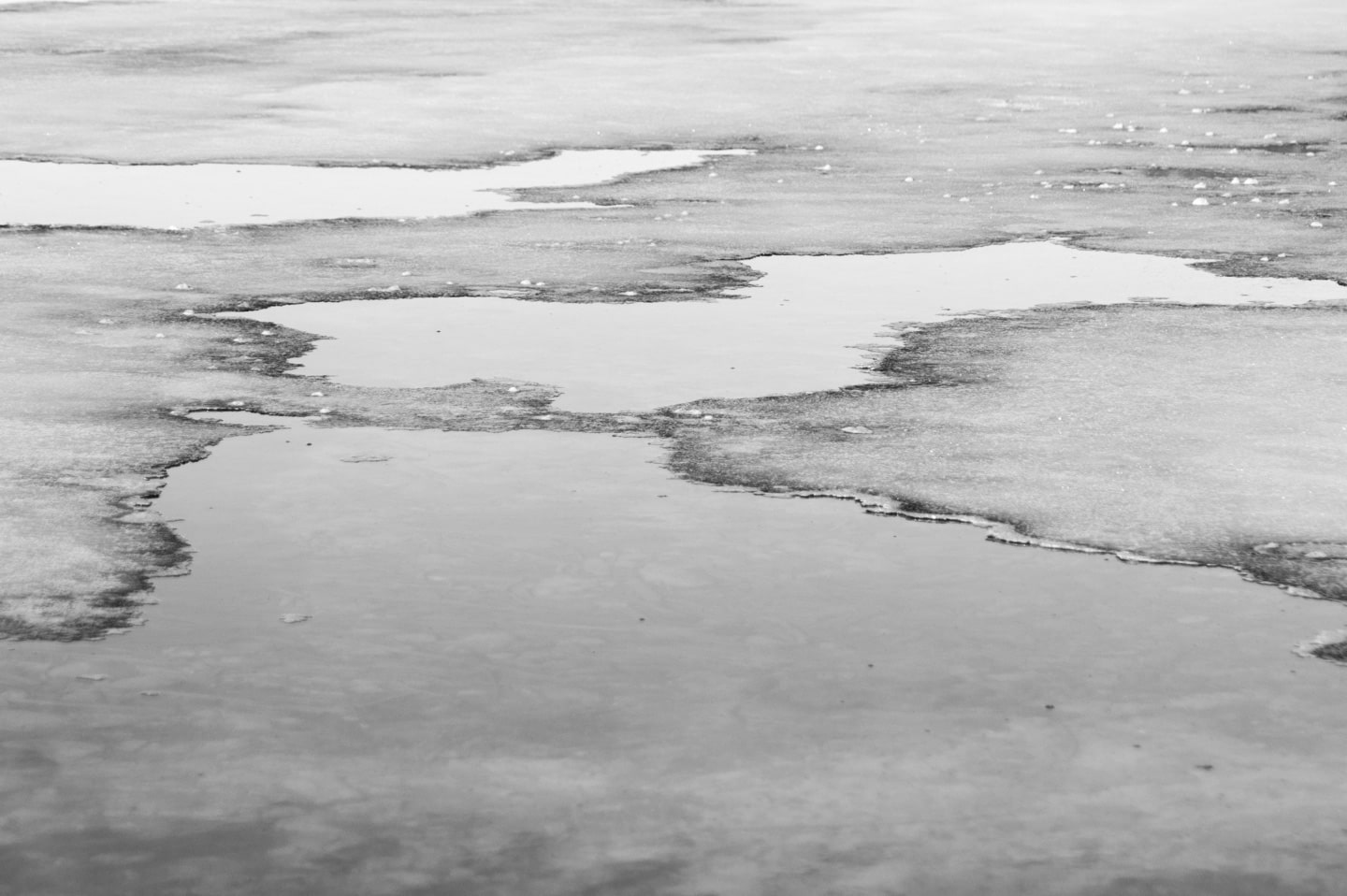 A black and white photograph of ice melting in the shallows of a clear lake. The ice is thin and flat, sparkling in the afternoon light, and the water is glassy calm, reflecting the clear luminous sky.