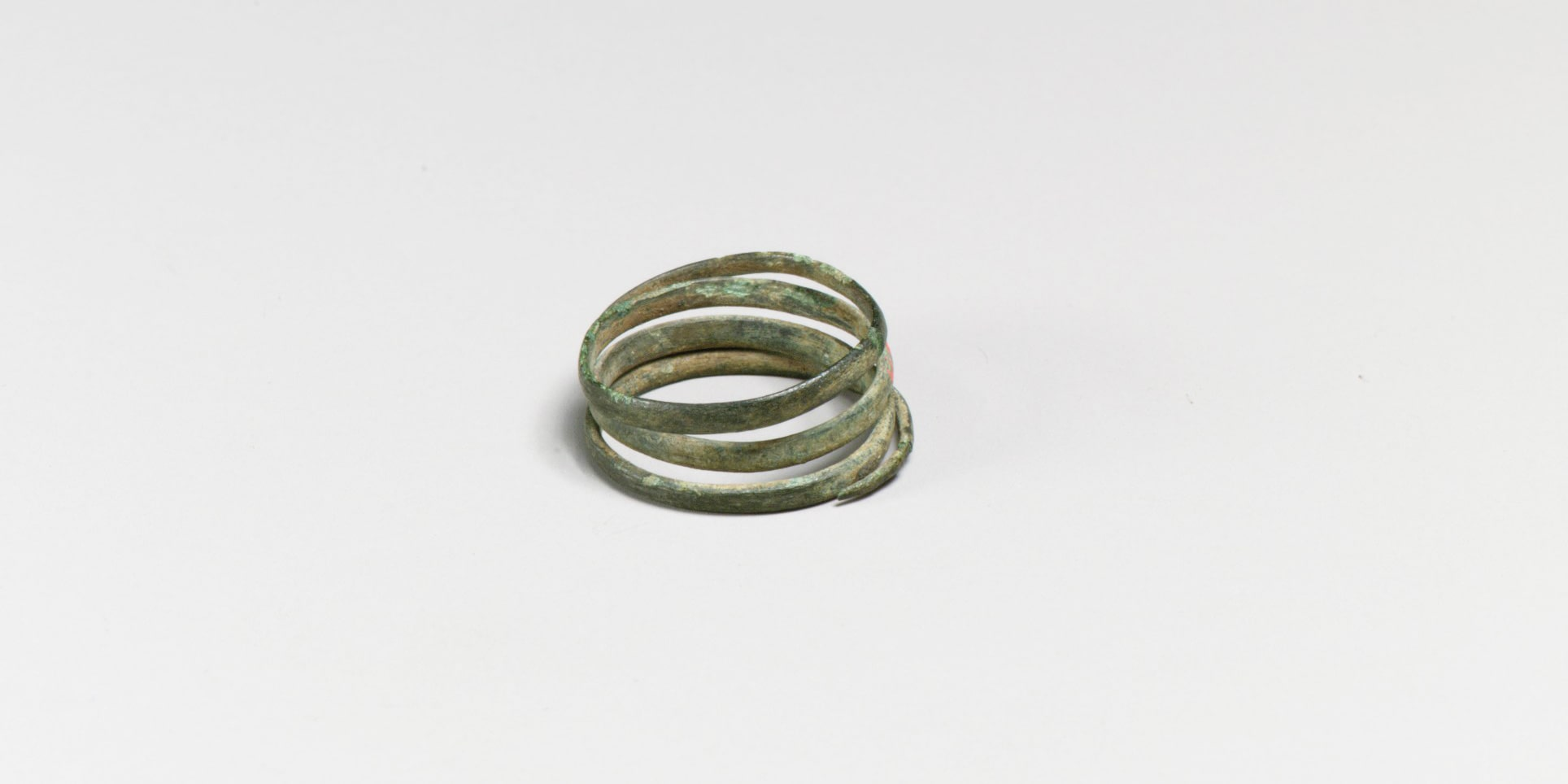 A photograph of a small spiral of flattened bronze wire against a featureless gray background. The spiral comprises four loops and its surface is dull and oxidized turquoise in places.