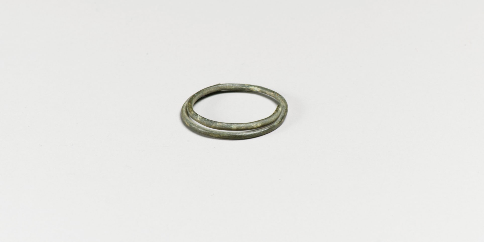 A photograph of another bronze spiral. The wire is round and the spiral comprises a loop and a half.