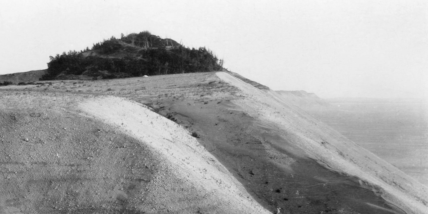 A black and white photograph, taken sometime in the 01920s, of the brink of a moraine high over the flat water of Lake Michigan. In the foreground, the westward face of the bluff is illuminated gently by the afternoon sun. At the horizon stands a perched dune covered in a dense stand of cedars, silhouetted nearly black against a hazy sky. Before the dune sits a luminous white boulder nestled into the till.