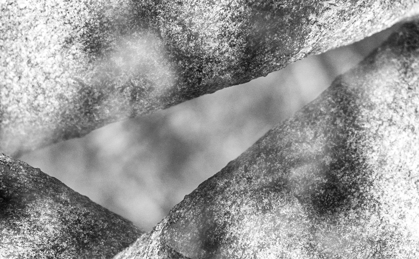 A black and white composite photograph of a rough granite surface in front of a dappled, out-of-focus background. The photograph is copied three times and rotated so the straight edges of stone form a thin obtuse triangle identical to the one described in the text.